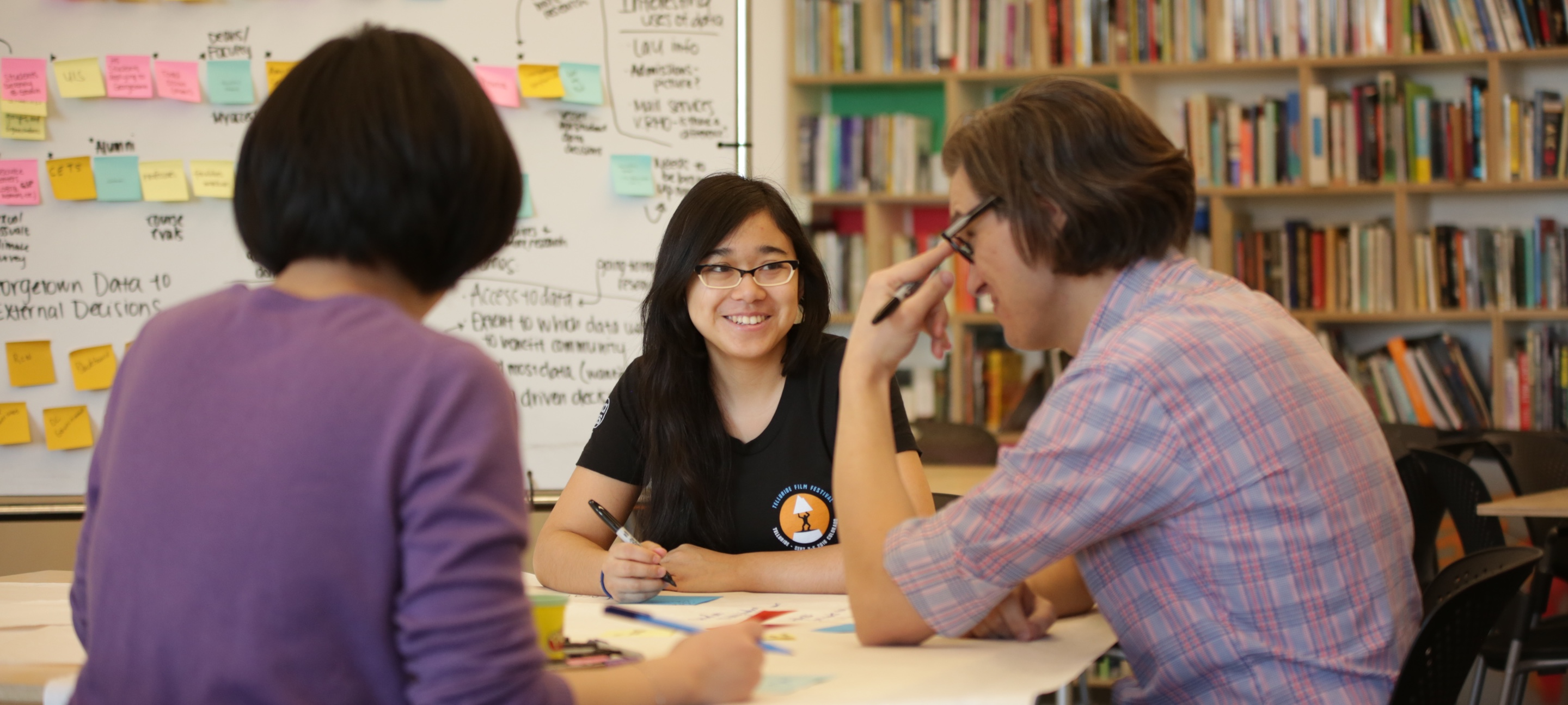 Three students collaborate during a design workshop.
